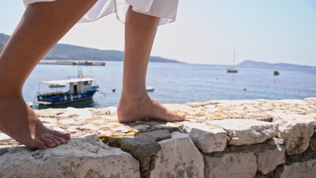 SLO MO Walking barefoot on a pier made of stone