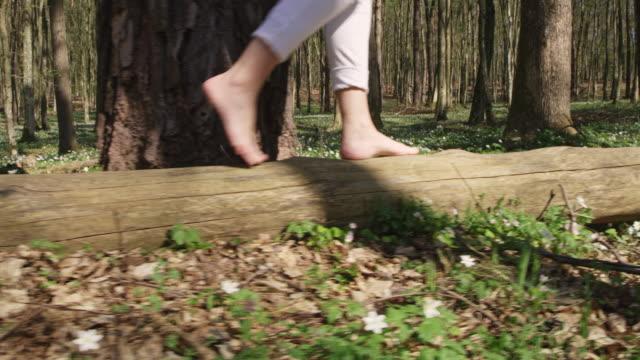 vídeos de stock, filmes e b-roll de ws la andando descalço em um tronco de árvore - tronco termo anatômico