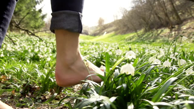 stockvideo's en b-roll-footage met hd super slow-mo: walking barefoot over spring snowflakes - blootvoets