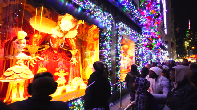 Walking Camera captures crowd at front of Saks Fifth Avenue window displays, which are illuminated by 2016 Saks Fifth Avenue Holiday Light Show at night in Midtown Manhattan.
