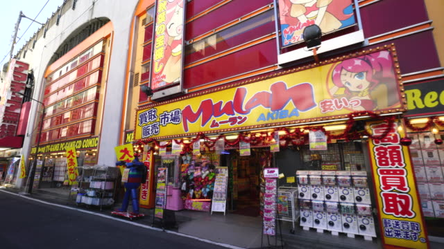 walking camera captures many game soft shops, anime shops and electric shop along the street under the jr line in akihabara, chiyoda-ku tokyo. - toy store stock videos and b-roll footage