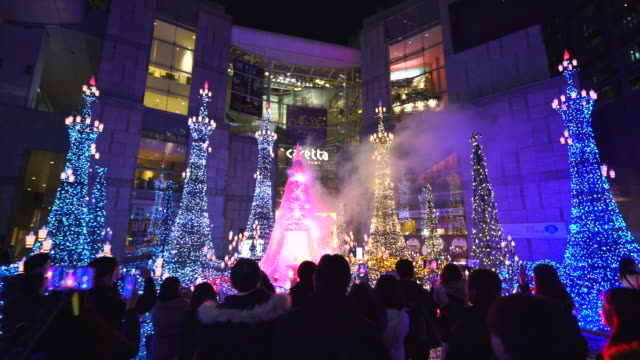 walking camera captures people enjoying to watching and photographing the caretta illumination show, which is illuminated by approximately 250,000 led lights every 20 minutes in caretta shopping mall shiodome tokyo japan on january 16 2018. - disney stock videos & royalty-free footage