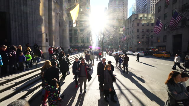 Walking camera goes through the crowded 5th Avenue and captures Saint Patrick's Cathedral and crowded Saks Fifth Avenue at Midtown Manhattan in Winter Holidays 2016. Exterior of Saks Fifth Avenue and window displays are decorated for Christmas decoration.