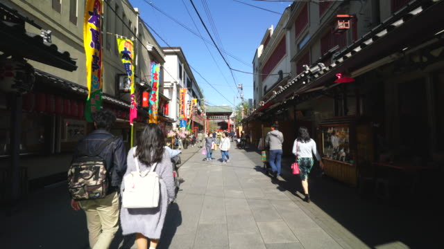 walking camera is going through the okuyama omairimachi shopping street at asakusa, tokyo.camera captures traditional japanese gift shops and restaurants and a public theater along the street. - randoseru stock videos & royalty-free footage