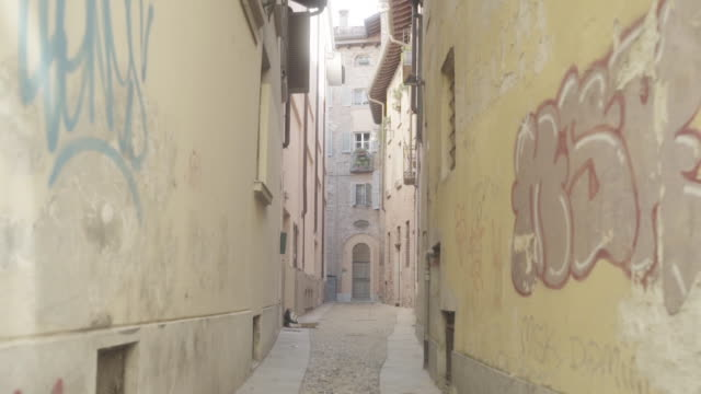 pov, walking down graffitied alleyway in italy - alley stock videos & royalty-free footage