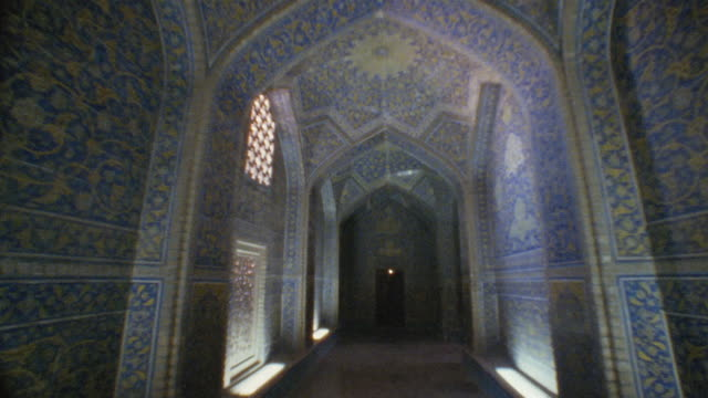 ws walking pov down sheikh lotfollah mosque corridor/ turning into domed room with sunbeams coming through windows/ isfahan, iran - モスク点の映像素材/bロール