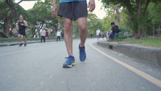 vídeos de stock e filmes b-roll de walking exercising in the park - roupa desportiva