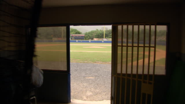exiting storage room into ballpark, diamond w/ dirt base paths & pitching mound, blue outfield wall, trees & mountains bg, stands w/ rows of seats,... - gabbia di battuta video stock e b–roll