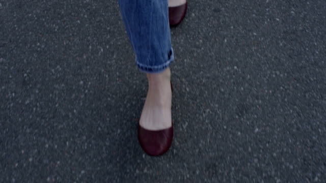walking feet of woman in two directions in jeans on asphalt in slow motion - footpath stock-videos und b-roll-filmmaterial
