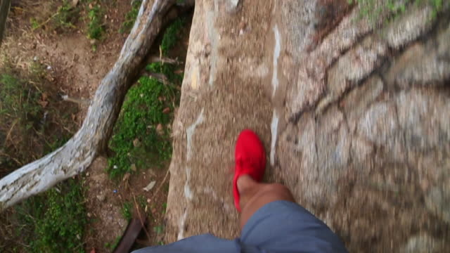 Walking from personal point of view with red shoes in a narrow path in the beach of the Girona Costa Brava.