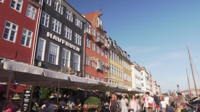 walking handheld view: crowds enjoying restaurants bars among colorful traditional houses in copenhagen nyhavn city, denmark - travel destinations stock videos & royalty-free footage