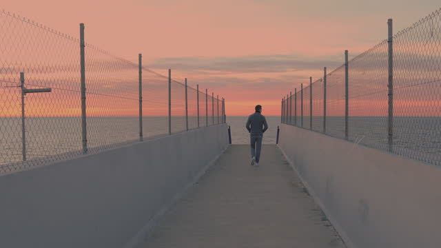 walking in elevated walkway to the sea with stunning view during sunrise. - vanishing point stock videos & royalty-free footage
