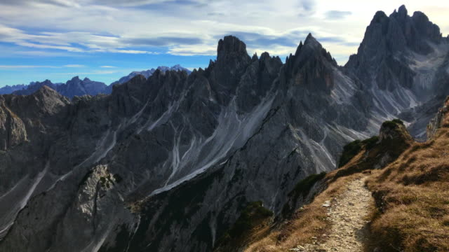 vidéos et rushes de walking in footpath with the sharp dolomite mountains in the italian alps. - vertige