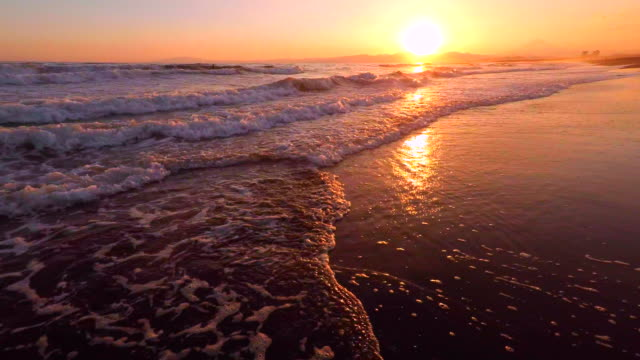 walking in to the sea at sunset -4k - surf stock videos & royalty-free footage