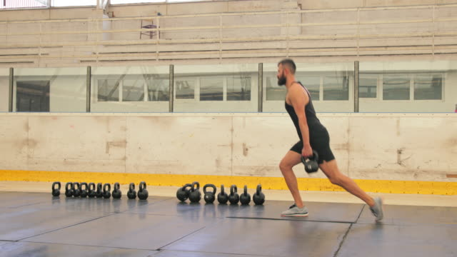 Walking lunges with kettlebells, panning shot