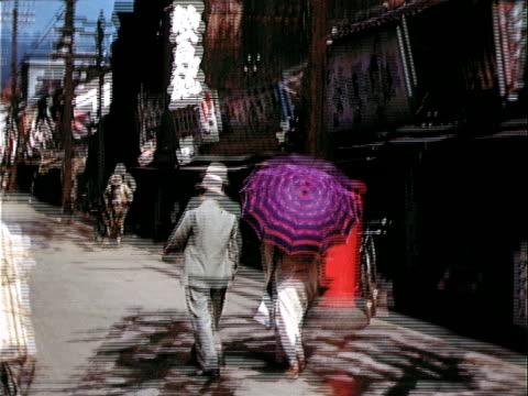 1939 walking pov man in suit and woman in kimono with umbrella walking down city street/ japan - 1930~1939年点の映像素材/bロール