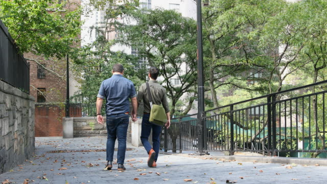 walking mature adult gay men holding hands in new york - romance stock videos & royalty-free footage