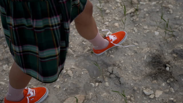 walking on a dry, rocky ground. red shoes and funny socks - dry clothes stock videos and b-roll footage