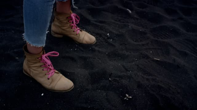 Walking on black sand. Close up on shoes
