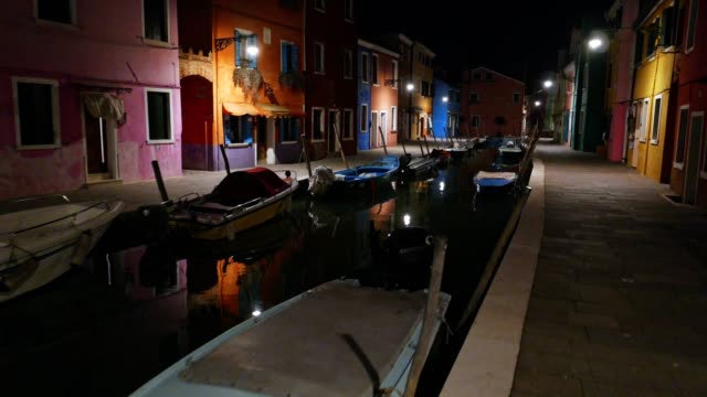 POV walking on Burano island at night, Venice, Italy, city of romance, typical venetian sights, part of series, travel destinations, colourful houses of a fishermen village illuminated by the street lights