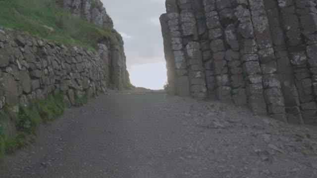 wandern auf riesendamm sonnenuntergang, nordirland - nordirland stock-videos und b-roll-filmmaterial