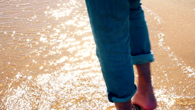 Walking on golden sand through shallow sea water. Single man bare feet rear view.