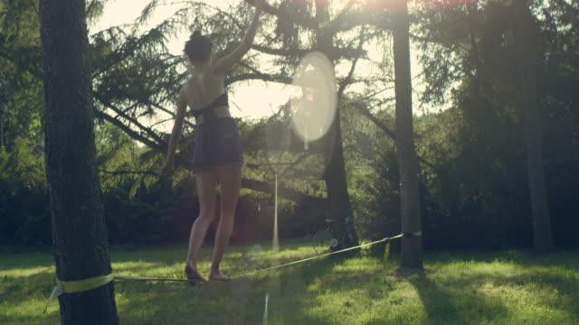 walking on slackline. summer afternoon in park - freizeit stock-videos und b-roll-filmmaterial