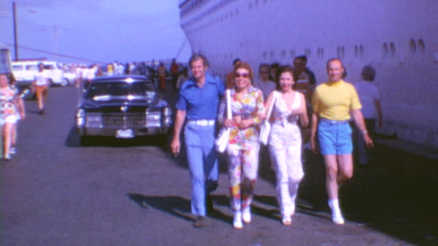 walking past cruise ship / song of norway hull / couple hugging / wide shot of ship on august 01 1972 in cape canaveral florida - kreuzfahrt stock-videos und b-roll-filmmaterial