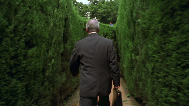 rear view walking point of view businessman walking in maze coming to dead end + trying to find exit - looking around stock videos & royalty-free footage