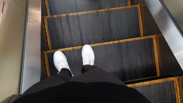 4k walking point of view . feet moving down and getting off escalator - escalator stock videos & royalty-free footage