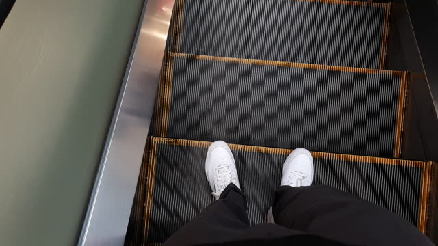 walking point of view . feet moving down and getting off escalator - walking point of view stock videos & royalty-free footage