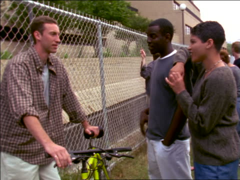 Walking point of view group of multi-ethnic teens hanging out by chain link fence outside school talking