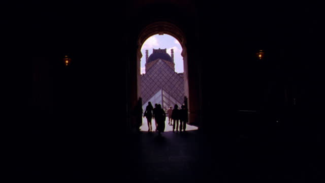 walking point of view in dark towards arch opening with silhouettes of people / pyramide + louvre in background / paris - punto di vista di un passante video stock e b–roll