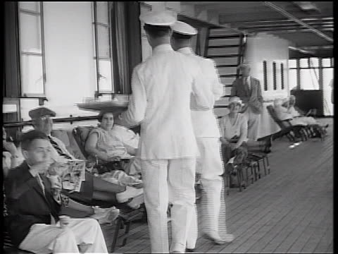 b/w 1934 walking point of view ship passengers relaxing in chairs on deck / waiters serving refreshments - passenger点の映像素材/bロール