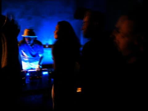 vídeos de stock e filmes b-roll de walking point of view through dancing crowd towards male disc jockey spinning records in club / santa monica, california - super exposto