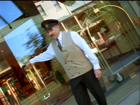 vídeos y material grabado en eventos de stock de walking point of view through glass door being opened by doorman into hotel lobby / australia - entrada