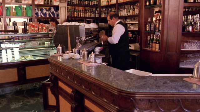 walking point of view toward waiter putting coffee cups on counter / waiter with tray passes in foreground / florence - bar video stock e b–roll
