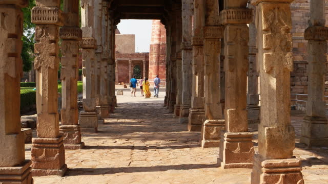 a walking pov through the intricate stone carvings on the cloister columns at qutb complex,  pillars taken from hindu temples, towards the majestic qutb minar, the victory tower - minareto video stock e b–roll