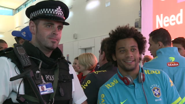 Walking shot of Marcelo as Brazil arrives for London 2012 olympics / poses for picture with armed London policeman wearing headphones around his neck...