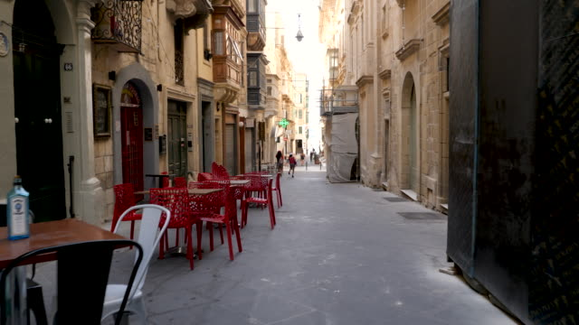 4k pov walking shot through the back streets of valletta. shows single lady eating at restaurants and bars nestled in small alleyways and passages, perfect for tourists to explore whilst on holiday - public celebratory event stock videos & royalty-free footage