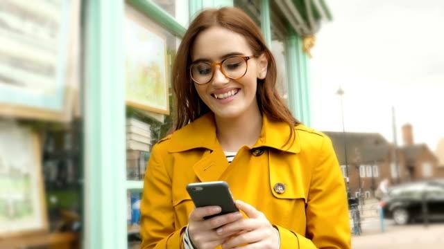 stockvideo's en b-roll-footage met wandelen glimlachend lezen telefoon bericht. jonge vrouw die een regenjas draagt. - ingesproken bericht