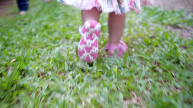 walking step of little girl on grass , slow motion - lawn stock videos & royalty-free footage