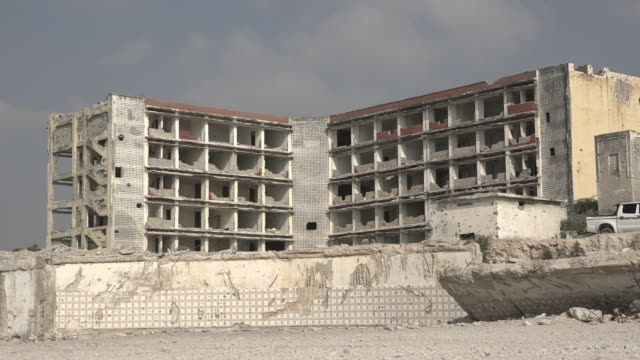 walking the destroyed streets of old mogadishu in somalia where children are playing football among the rubble - rubble stock-videos und b-roll-filmmaterial