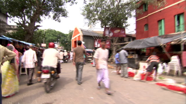 walking through a busy kolkata marketplace towards a pandal set up for the hindu festival of durga puja. available in hd. - kalkutta stock-videos und b-roll-filmmaterial