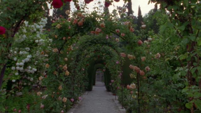 Walking POV through flower-covered arches in Generalife Gardens/ Alhambra, Spain