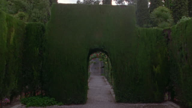 Walking POV through sculpted bushes and flower-covered arches in Generalife Gardens/ Alhambra, Spain