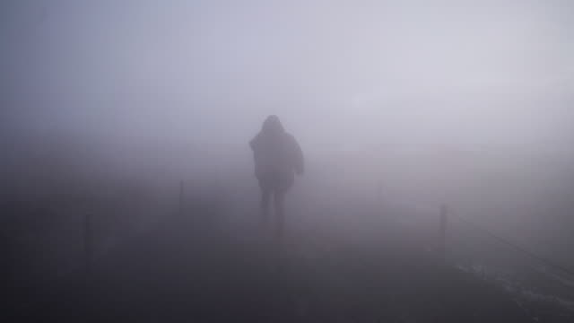 vídeos de stock e filmes b-roll de walking through thick fog on iceland - casaco curto com mangas