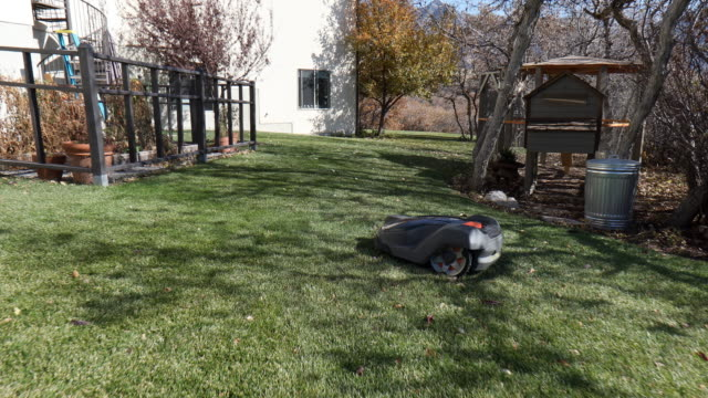 walking through yard as robotic auto lawn mower cuts grass - grass stock videos & royalty-free footage
