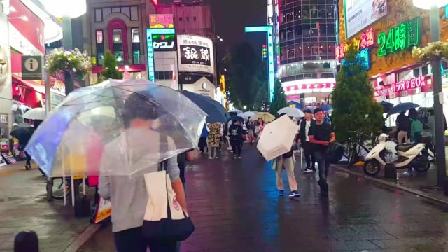 walking time lapse crowd people walking and crossing road in the city while raining - banner sign stock videos & royalty-free footage