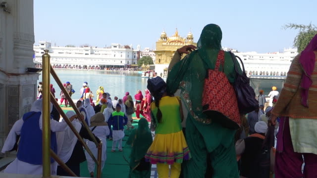 walking towards promenade with view of golden temple, amritsar - punjab india stock videos and b-roll footage